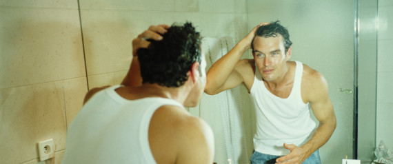 Man looking at reflection in bathroom mirror, wet face and hair